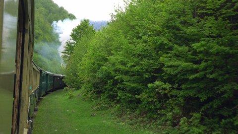 view from the window of a retro train wagon, Old steam locomotive in Romania, Steam narrow gauge train, Steam train chugging through the countryside, narrow-gauge railway
