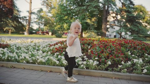 Little baby girl walking outdoor near blossom flowerbed