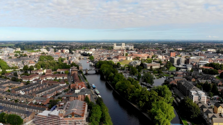 Aerial footage of the town of York located in North East England and founded by the ancient Romans, the footage shows the York Minster Historical Cathedral in the main town centre along the river. | Shutterstock HD Video #1036686479
