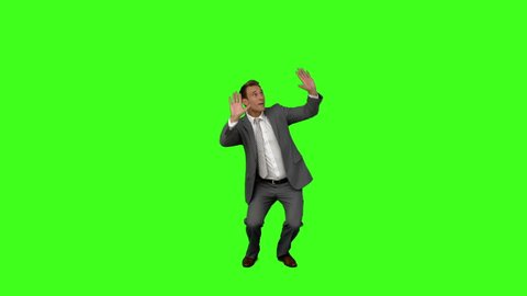 Businessman standing and cowering on green screen background