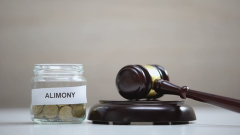 Alimony glass jar with coins on table, gavel striking on sound block, government