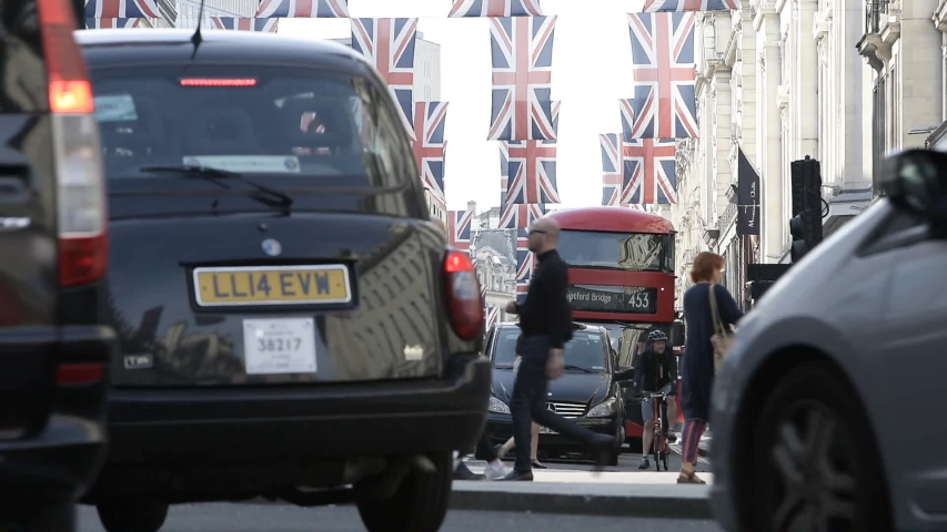 London, United Kingdom - Circa 2019: Pedestrians walking in central London on Regent street in London with Union Jack flags above before Royal Marriage - low angle view through cars and taxis | Shutterstock HD Video #1036872389
