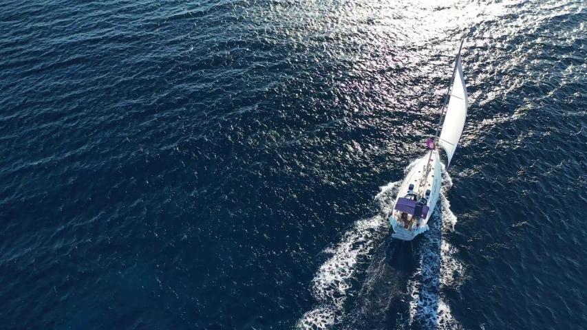 Aerial drone birds eye view video of beautiful sail boat cruising in the deep blue Aegean sea, Greece #1036922309