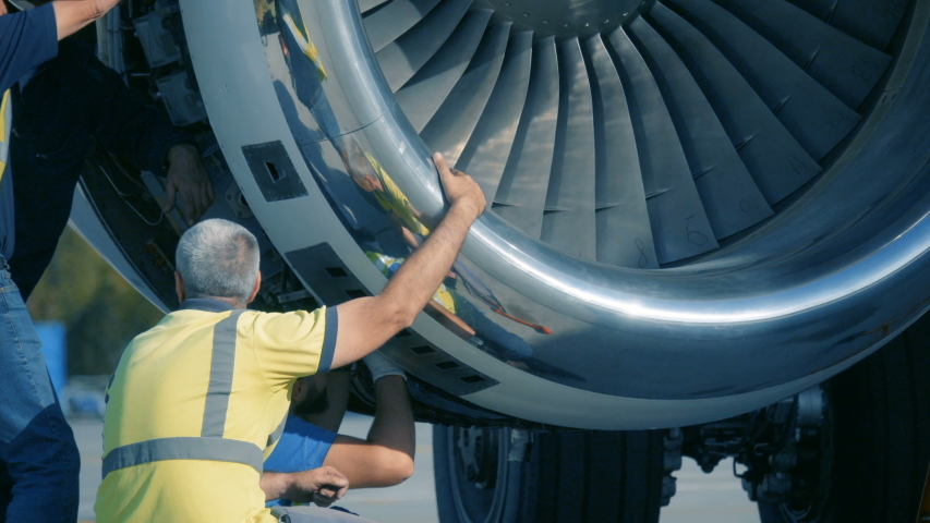 Aircraft Mechanics and Engineers  Diagnose and repairing jet engine through open hatch. Airplane turbine repair