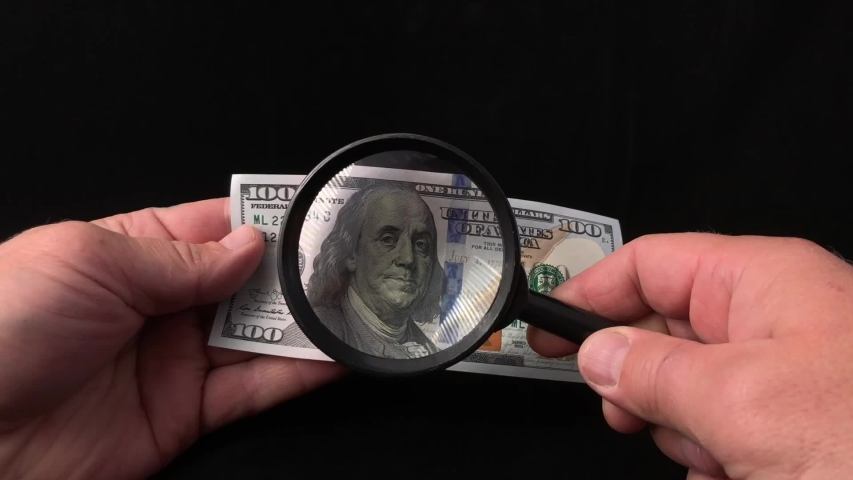 A man checks dollars through a magnifying glass. In the man's hands is a magnifying glass and one hundred American dollars. Check the hundred dollar bill for a fake. Careful consideration of money. | Shutterstock HD Video #1036939409