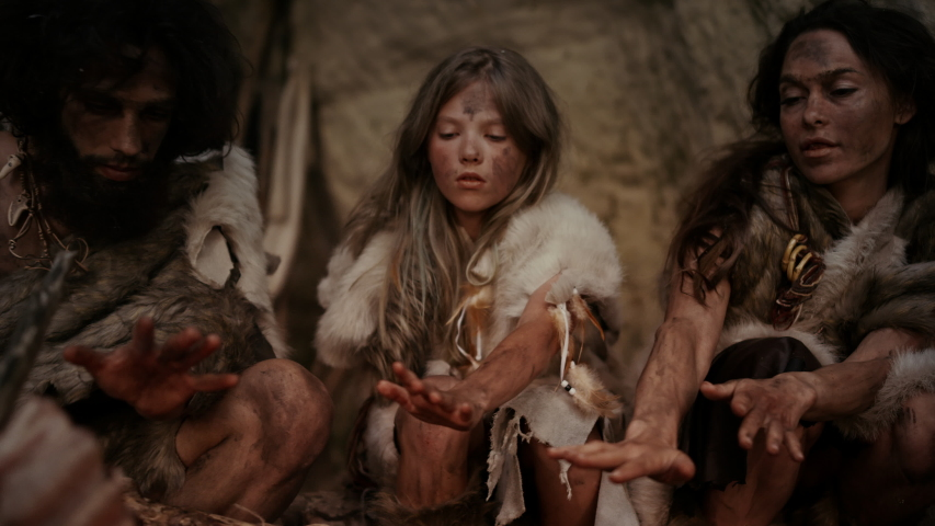 Tribe of Prehistoric Hunter-Gatherers Wearing Animal Skins Live in a Cave at Night. Neanderthal or Homo Sapiens Family Trying to Get Warm at the Bonfire, Holding Hands over Fire, Cooking Food | Shutterstock HD Video #1037018339