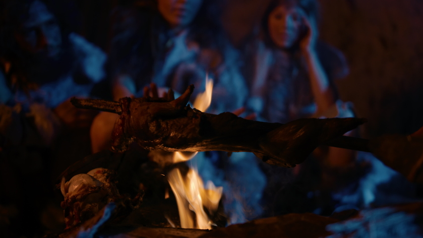 Neanderthal or Homo Sapiens Family Cooking Animal Meat over Bonfire and then Eating it. Tribe of Prehistoric Hunter-Gatherers Wearing Animal Skins Grilling and Eating Meat in Cave at Night | Shutterstock HD Video #1037018759