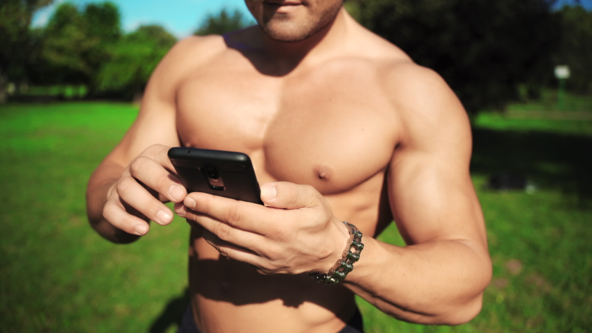 Young attractive fitness trainer chatting online with clients using his modern technologies smartphone. Training classes online, instructions for effective workout in the gym and the most important | Shutterstock HD Video #1037037509
