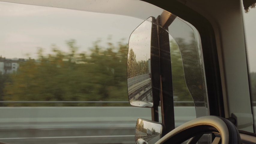 Truck driver rides to destination. View for window and mirror.Man  driving car at country road on warm summer day. View from the lorry cab. Slow motion Close up | Shutterstock HD Video #1037110379