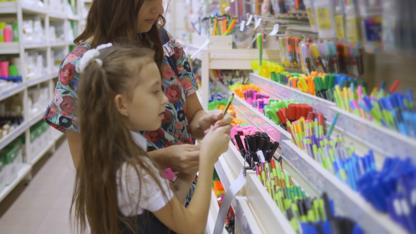Purchase of school supplies. Mother and daughter in supermarket stationery. | Shutterstock HD Video #1037198789