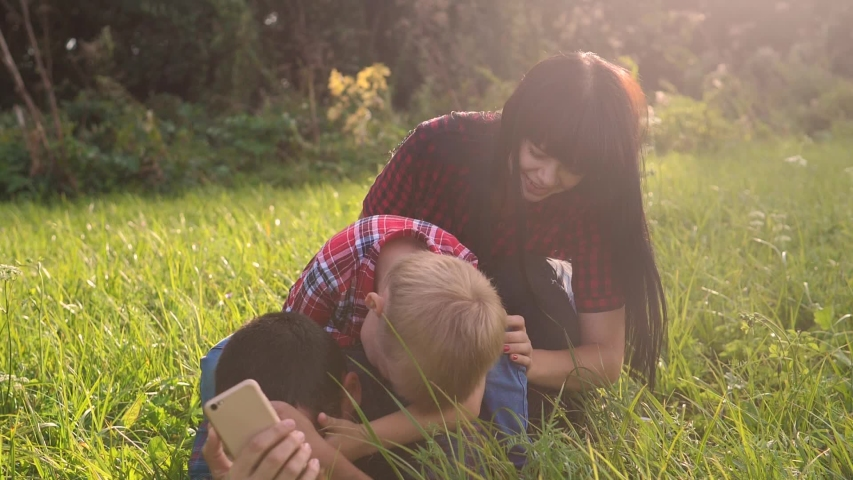 Happy family teamwork outdoors have fun concept outdoors slow motion video. mom dad and son take a photo with a smartphone lifestyle in nature are sitting on the grass have fun playing .mom girl dad   Shutterstock HD Video #1037217989