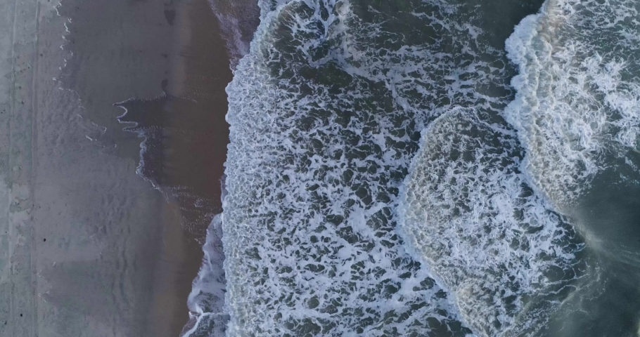 Aerial bird's-eye view of beach and waves of teal water flowing to the coast | Shutterstock HD Video #1037224229