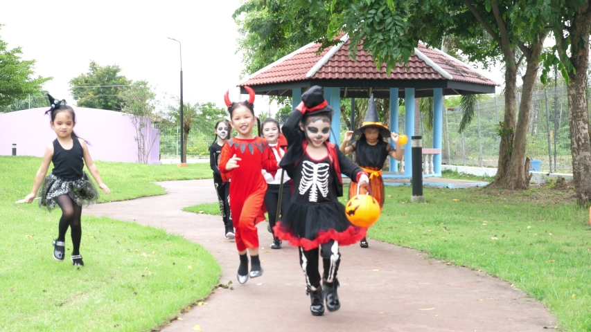 Group of asian children in halloween costume running in park. | Shutterstock HD Video #1037237399