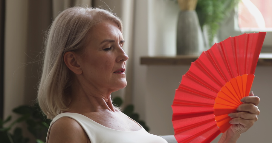 Overheated old senior woman feel hot wave fan annoyed with high temperature sit at home, stressed middle aged lady sweating suffer from climax summer weather heat problem without no air conditioner | Shutterstock HD Video #1037252579