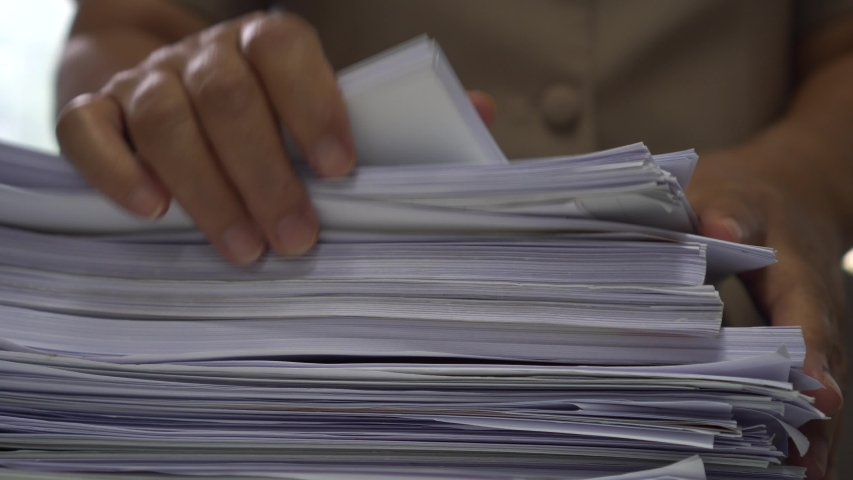 Businessman hands working in stacks of paper files for searching information on work desk office, business report papers,piles of unfinished documents achieves with clips indoor,Business concept | Shutterstock HD Video #1037268209