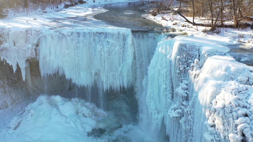Stream flowing over ice covered waterfall in winter with sun, aerial drone footage | Shutterstock HD Video #1037315129