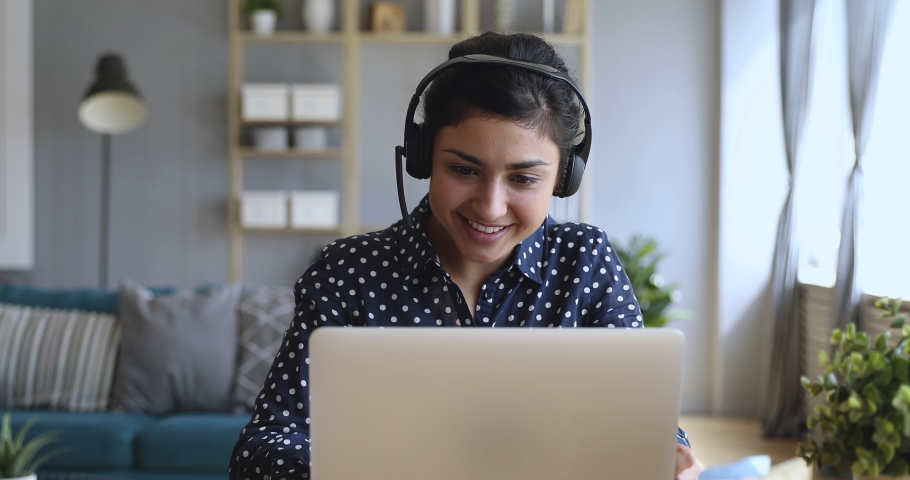 Smiling indian young business woman wear wireless headset video conference calling on laptop computer talk by webcam in online chat, customer support service and distance online teaching concept | Shutterstock HD Video #1037339309