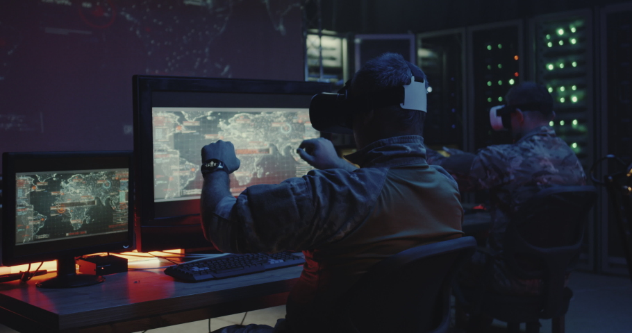 Medium shot of soldiers using VR headsets while sitting at their desks | Shutterstock HD Video #1037382599