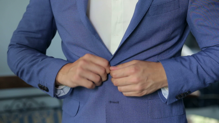 A man buttoning his jacket, close-up. A successful young man puts on a suit jacket in the morning. Businessman puts on a jacket. | Shutterstock HD Video #1037407829