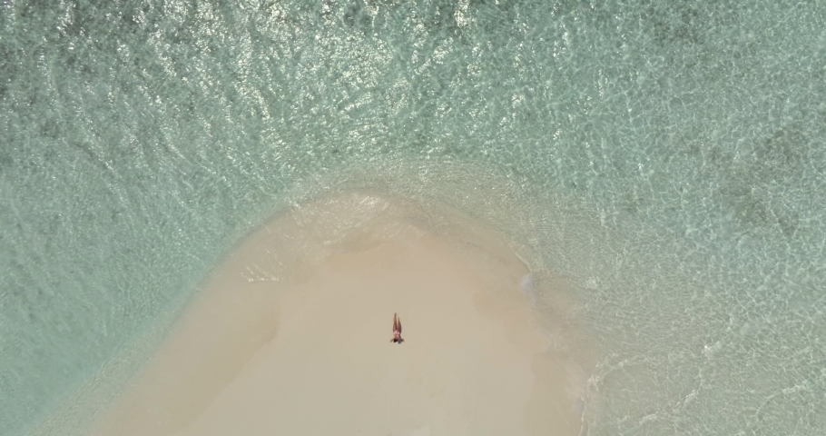 Aerial view of a sandbank in the Maldives sea - A young woman is lying on the white sand while looking at the sea | Shutterstock HD Video #1037507219