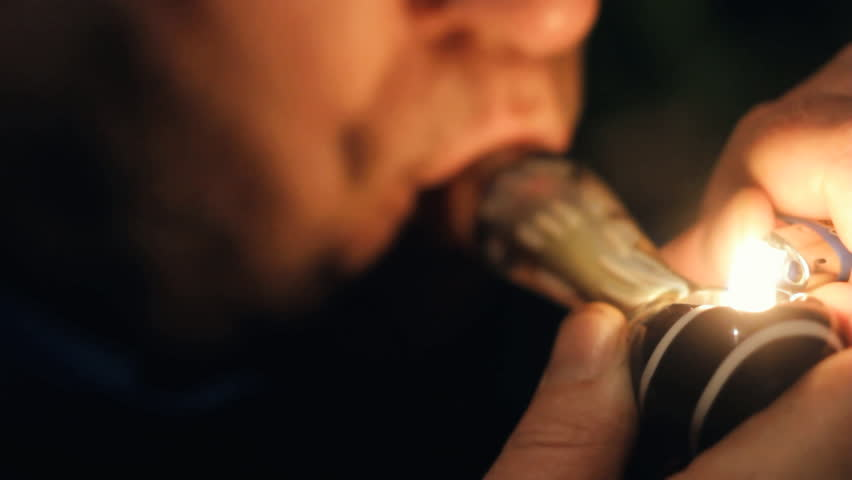 Man smoking marijuana or other drug from pipe at night