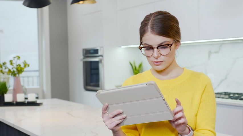 Beautiful girl with a tablet in the kitchen. European girl in a yellow sweater | Shutterstock HD Video #1037923499