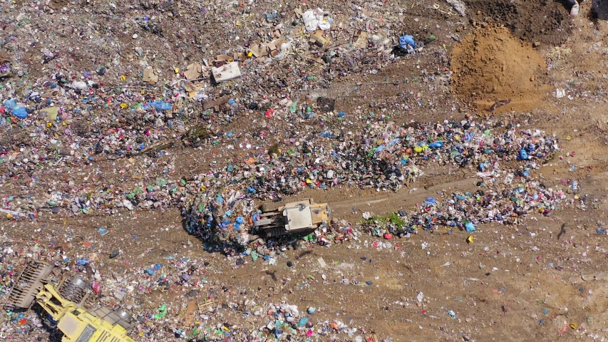 Top down aerial footage of a Municipal Solid waste Landfill during collecting, sorting and pressing work.   Shutterstock HD Video #1037987759