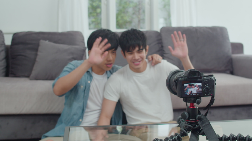 Young Asian gay couple influencer couple vlog at home. Teen korean LGBTQ men happy relax fun using camera record vlog video upload in social media while lying sofa in living room at house. Slow motion | Shutterstock HD Video #1038087149