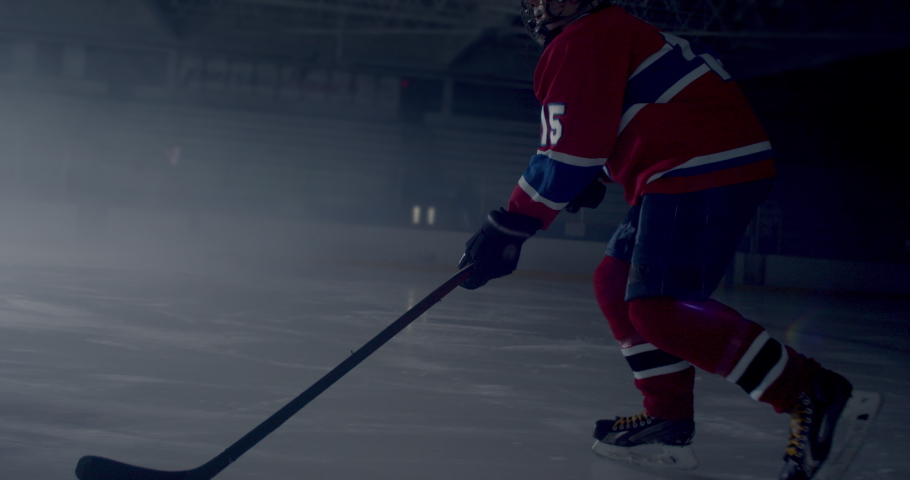 Hockey player skating in dramatically lit hockey rink skating and stick handling then taking a slap shot and scoring a goal as seen from behind hockey net | Shutterstock HD Video #1038217859