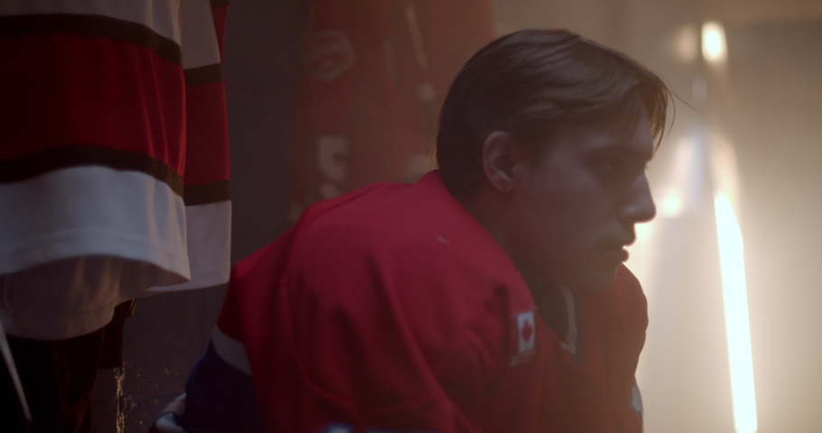 Focused and determined hockey player puts on helmet in change room getting ready putting on hockey equipment gets up and goes out to play  | Shutterstock HD Video #1038217889