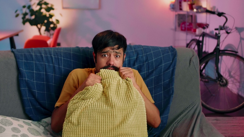 Handsome Hispanic man getting scared of horror movie watching alone at couch evening home, leisure violet light looking out of yellow pillow TV video content emotional guy sitting at sofa living room | Shutterstock HD Video #1038325259