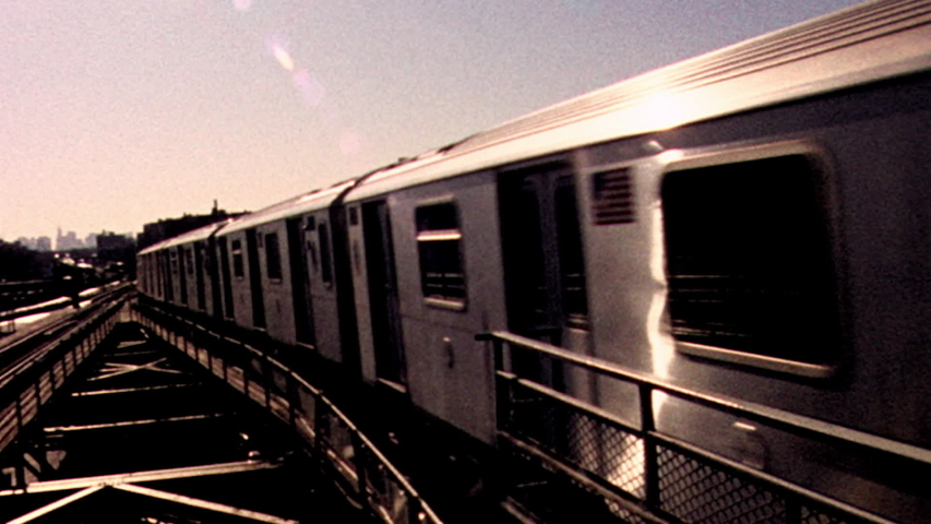 Retro looking archival footage of New York City subway train passing by with sun and city skyline in the distance