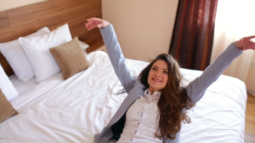 Young businesswoman entering in hotel room and lying on bed exhausted from the business trip. | Shutterstock HD Video #1038501959