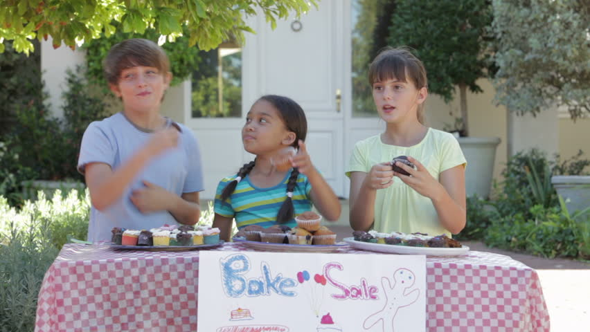 Three children at bake sale stall eating cakes are joined by mother before looking at camera.Shot on Canon 5D MkII at 25fps | Shutterstock HD Video #10387409