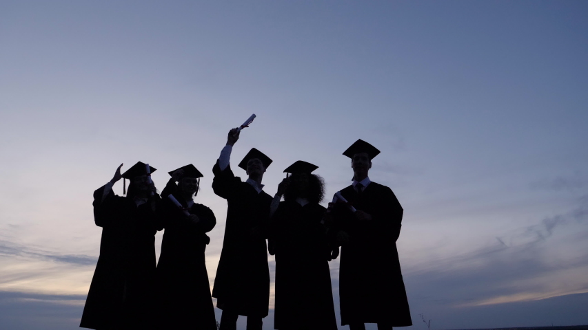 Silhouette of Graduating Students Throwing Caps In The Air. | Shutterstock HD Video #1038761039