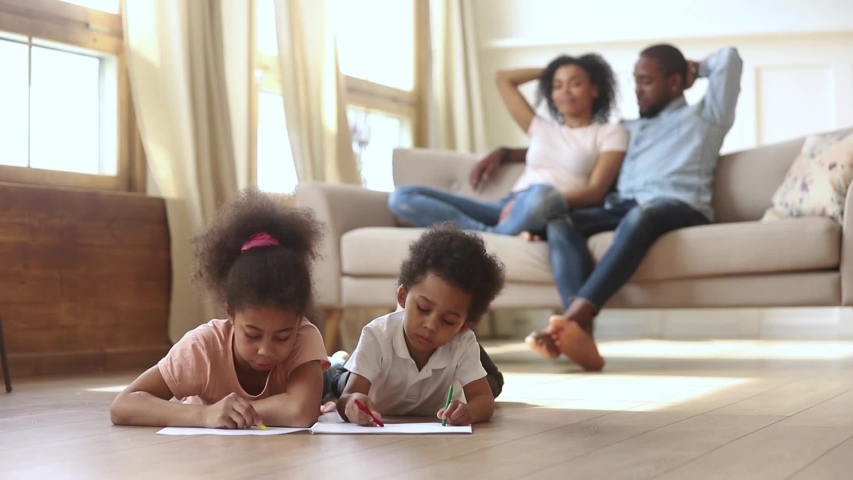Little mixed race african siblings lying on warm wooden floor in living room drawing with colorful pencils while young black mother and father resting, talking on couch activity at modern home concept | Shutterstock HD Video #1038796349