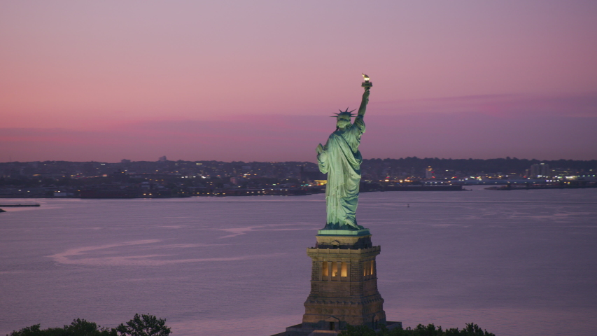 New York City, New York circa-2019. Aerial view of Statue of Liberty at sunrise. Shot from helicopter with Cineflex gimbal and RED 8K camera. | Shutterstock HD Video #1039113779