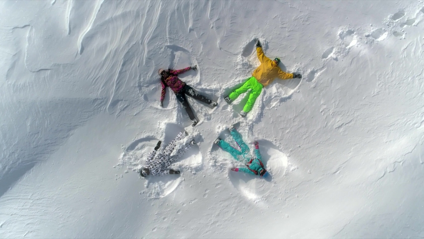 AERIAL TOP UP: a group of young people in bright ski suits depict snow angels lying on the fresh snow in the form of a cross. four winter angels happy and energetic with splashes of snow. SLOW MOTION