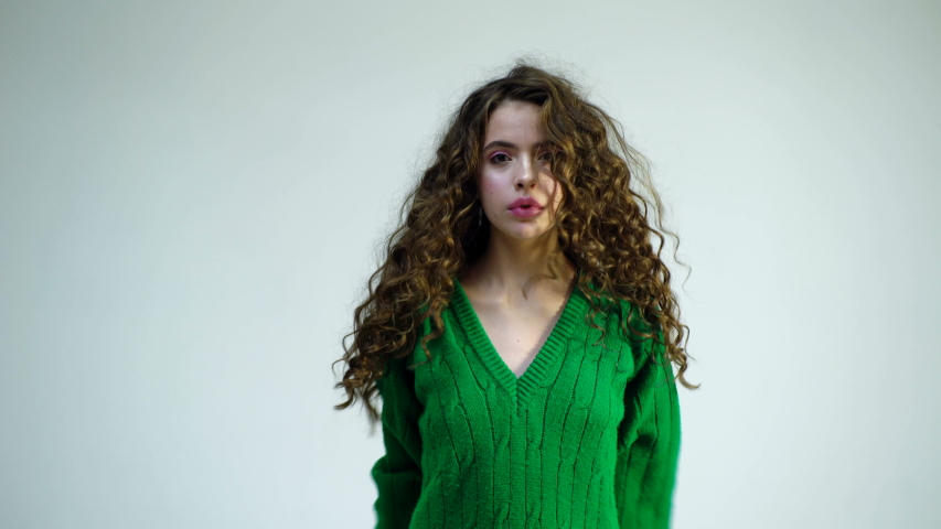 Funny girl with curly hair dancing isolated on a white backgroundParisian girl in winter clothes. Fashion look and beauty concept. Girl with curly hair dance at white wall background | Shutterstock HD Video #1039189979