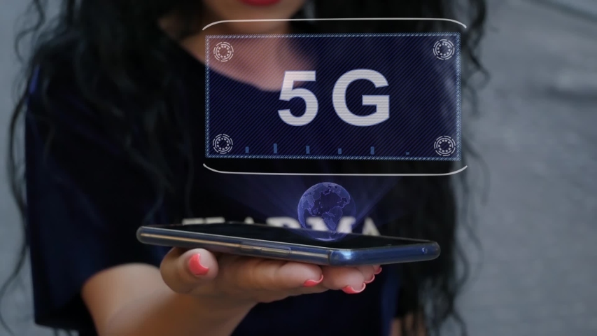 Unrecognizable curly brunette woman showing HUD hologram with text 5G. Girl uses technology of the future on a mobile screen | Shutterstock HD Video #1039205249