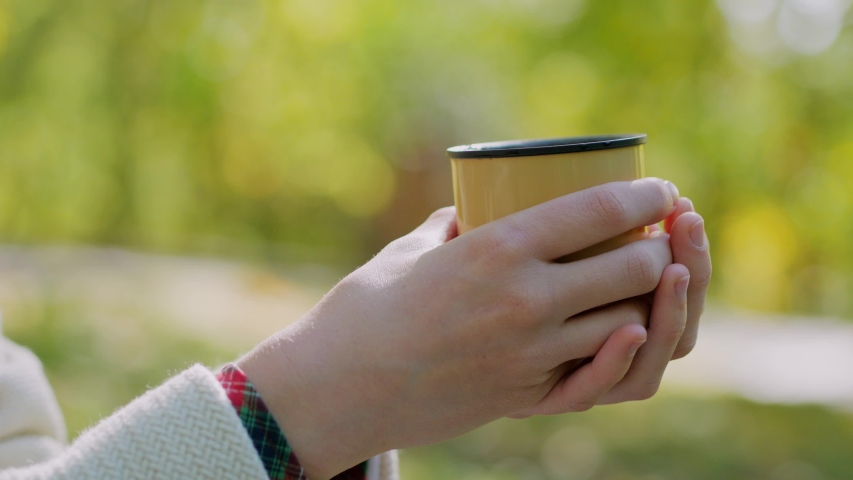 Cup of hot tea, young woman holding in hands, sitting on stairs in outdoors autumn park | Shutterstock HD Video #1039313219