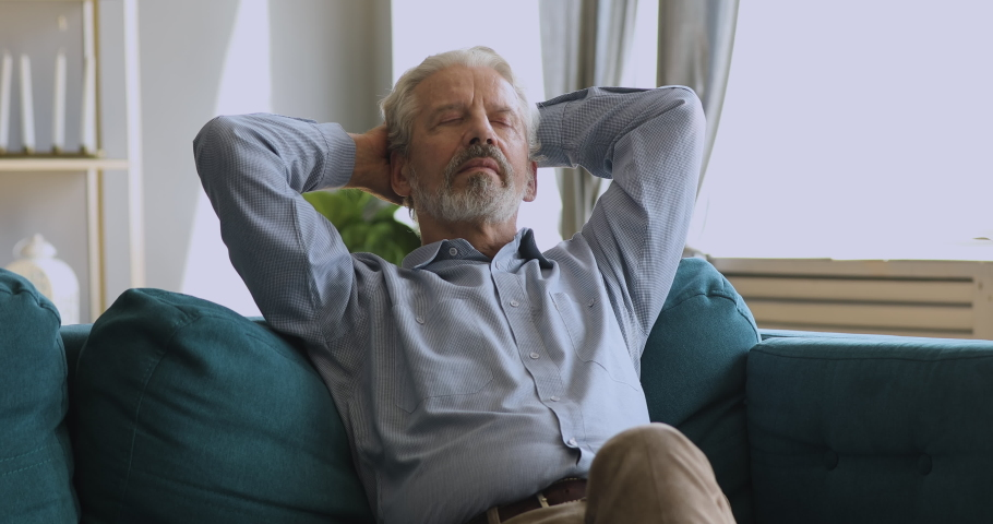 Healthy serene senior old man napping relaxing sit on couch at home, calm tranquil grandfather hold hands behind head on stress free peaceful day breathing fresh air rest on comfortable sofa indoors | Shutterstock HD Video #1039337969