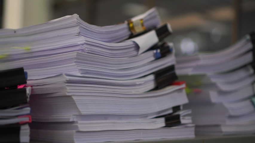 Piles unfinished documents reports files with overwork paper corner on teacher school desk office at university. Stack of messy paperworks assessment legal folder at workplace, tax audit concept | Shutterstock HD Video #1039371899