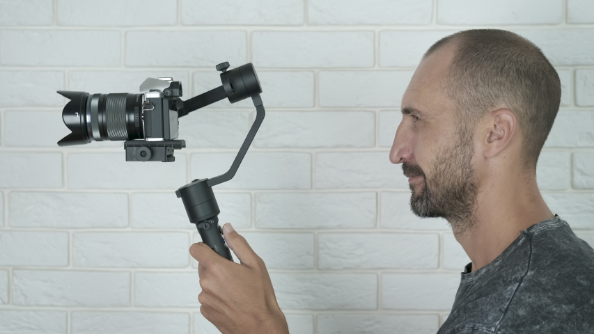 Man shoot a shot video. Cameras on an electronic stabilizer. Photographer taking video with a professional camera indoor. | Shutterstock HD Video #1039378919