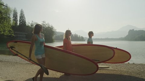 SLOW MOTION: Cheerful girl friends with stand up paddle boards walking to the lake and talking