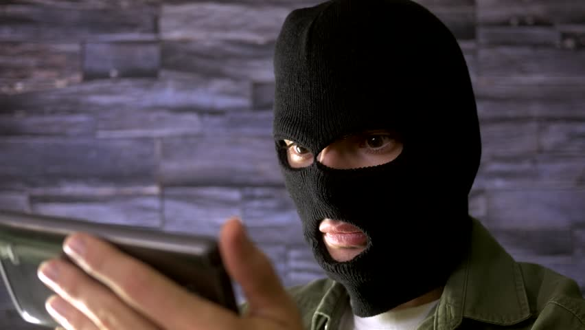 Criminal with a mask using a smartphone device to commit crime. | Shutterstock HD Video #10395791