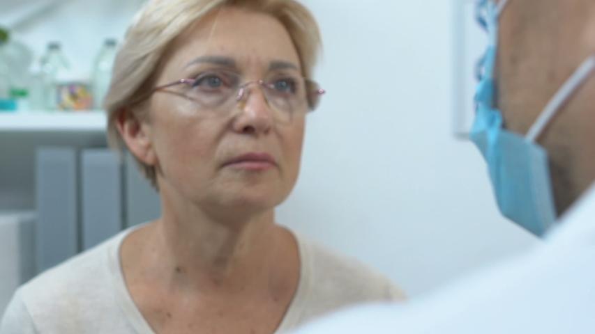 Otolaryngologist checking elderly female throat, angina symptoms and treatment | Shutterstock HD Video #1039581599