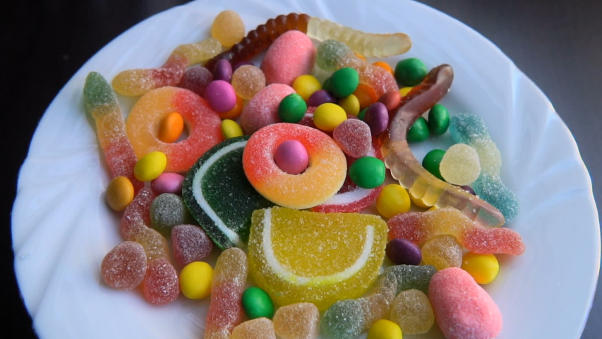 Yummy multicolored fruity candies are rotating on a turntable and camera is zooming in | Shutterstock HD Video #1039687049