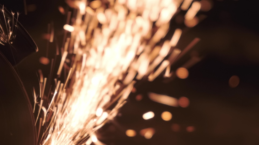 A big bunch of lawsuit from the work of a grinding saw that saws a metal pipe at night. Sparks look like a huge sparkler | Shutterstock HD Video #1039922309