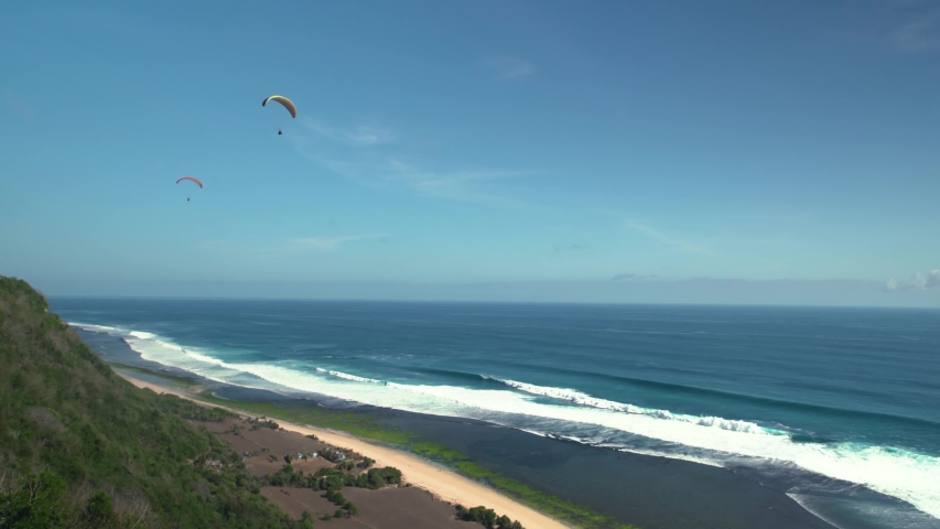 Paraglide fly above ocean coast line in Bali with scenic view 4K video | Shutterstock HD Video #1040015159